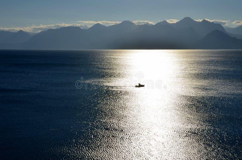 Einsames Boot bei Sonnenuntergang im Meer stockbild
