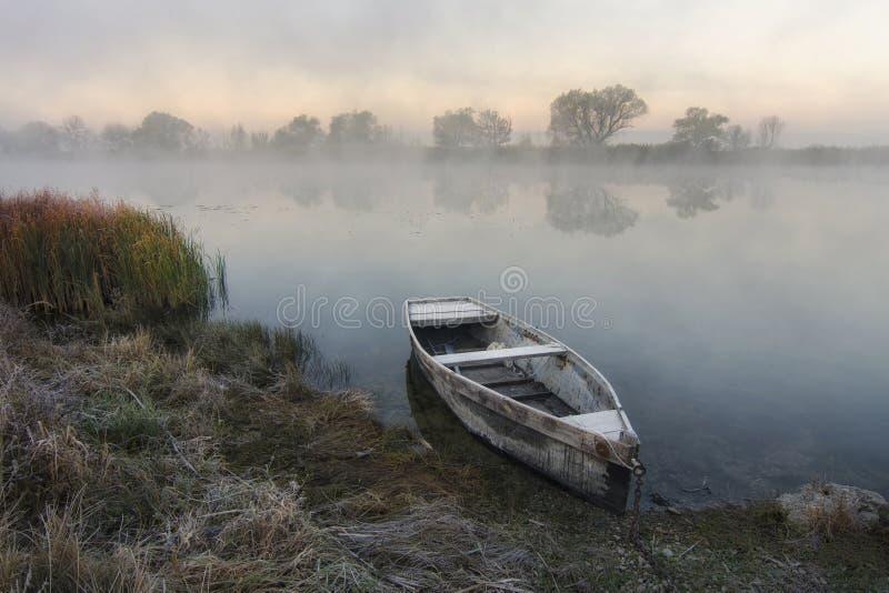 Einsames Boot durch den Fluss stockfoto