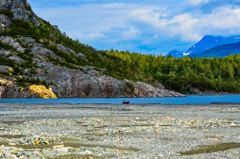 Einsames Kanu auf einem alaskischen Gletscher-Sediment-Strand lizenzfreie stockbilder