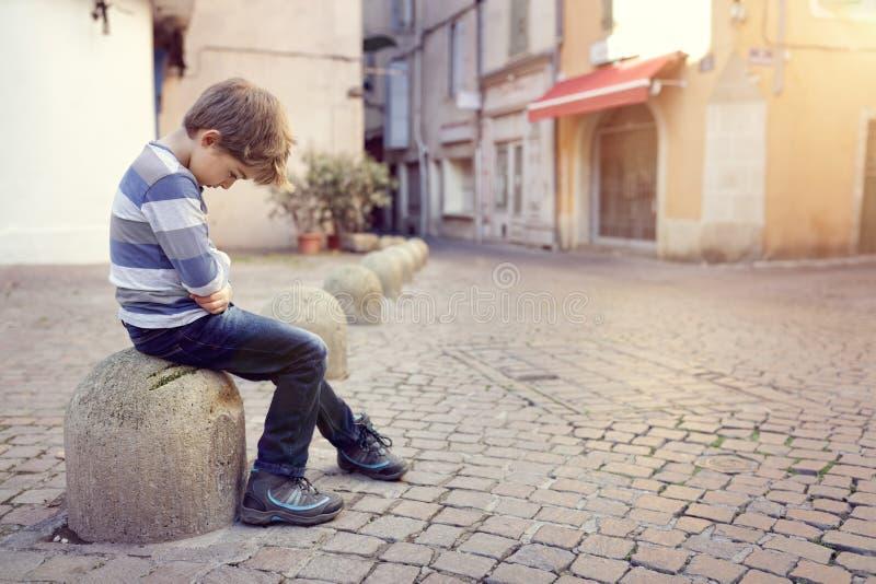 Einsames Kind, das auf einer Straßenecke sitzt lizenzfreie stockfotografie