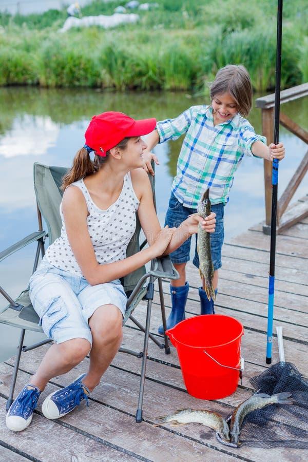 Einsames kleines Kinderfischen auf Fluss stockbild