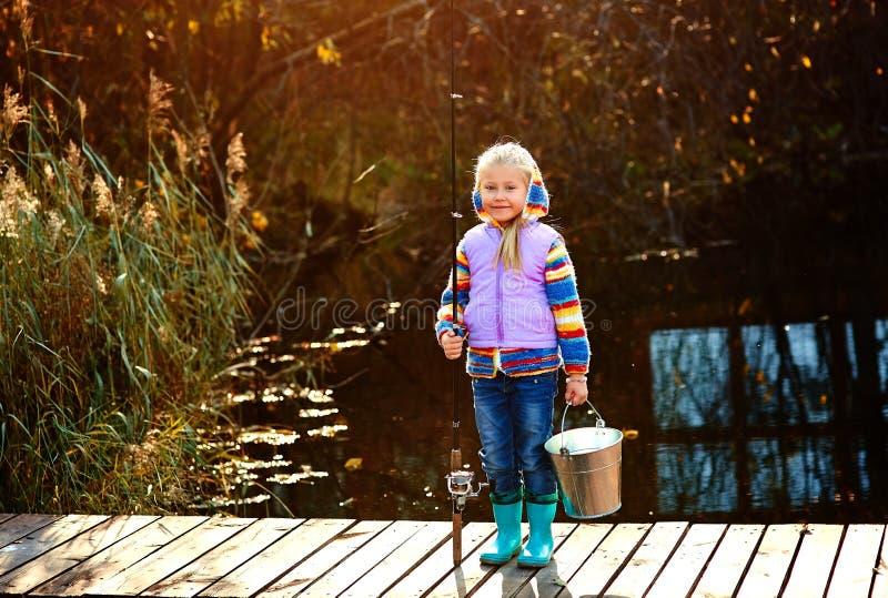 Einsames kleines Kinderfischen vom hölzernen Dock auf See stockfoto