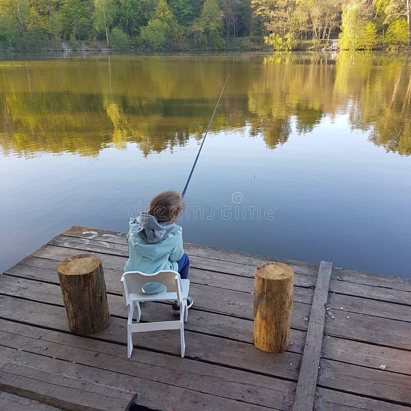 Einsames kleines Kinderfischen vom hölzernen Dock auf See lizenzfreies stockfoto