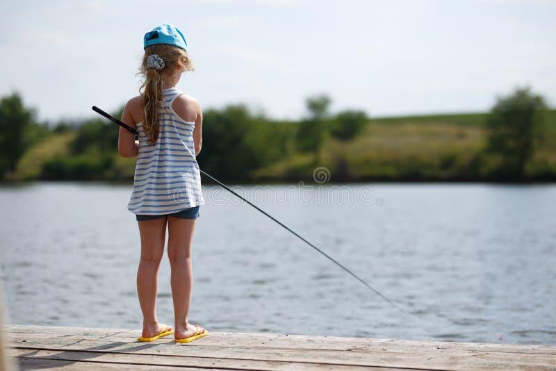 Einsames kleines Kinderfischen vom h?lzernen Dock auf See lizenzfreies stockbild