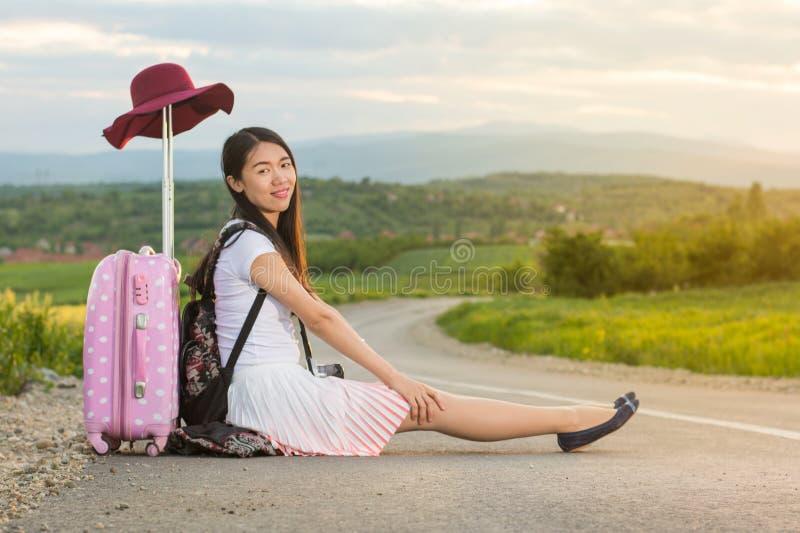 Einsames Mädchen, das auf der Straße sitzt stockfotografie