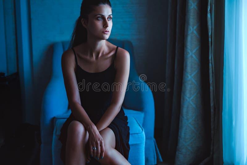 Einsames Mädchen, das am Fenster in einem Stuhl sitzt stockbild