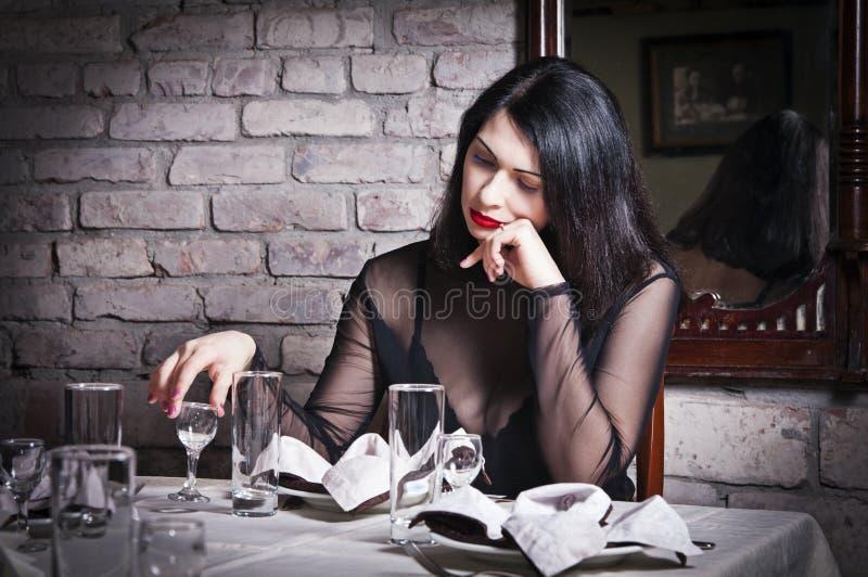 Einsames Mädchen, das am Restauranttisch sitzt stockbild