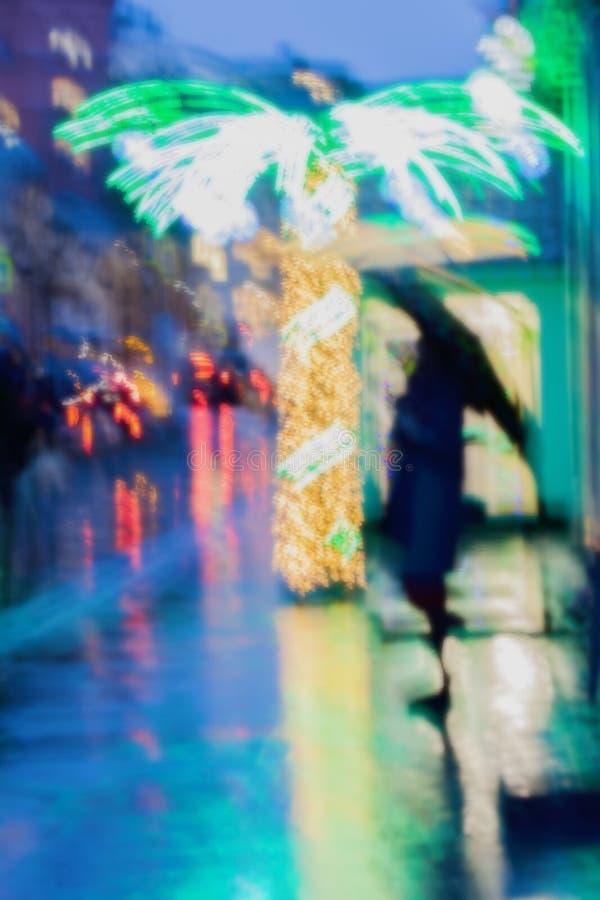 Einsames Mädchen unter einem Regenschirm auf dem Bürgersteig nahe bei einer belichteten Palme, Stadtstraße im Regen, helle Reflex stockfoto