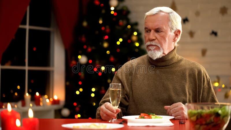 Einsames männliches Sitzen nahe funkelndem Weihnachtsbaum, der Champagner auf Weihnachtsabend isst lizenzfreie stockfotos