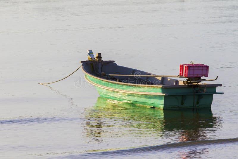 Einsames Metallboot, das auf Seestrand schwimmt stockfotografie