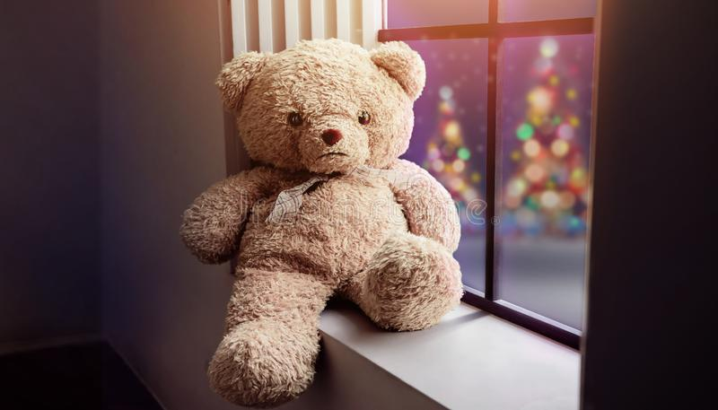 Einsames nahe gelegenes Fenster Teddy Bear Sittings im Haus auf Weihnachtsni stockfoto