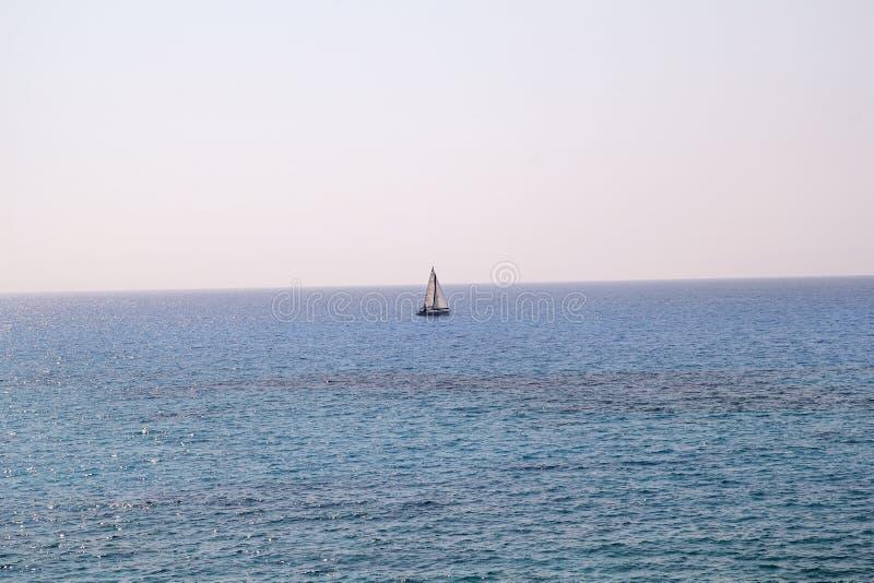 Einsames Schiff, Segelboot in hoher See Ruhiger See erlaubt bestes Segeln in der ruhigen Szene Wenig Segelboot auf Türkismeer stockfoto
