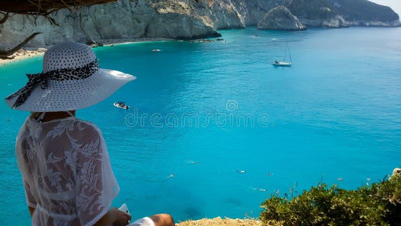 Einsames träumerisches Mädchen in einem weißen Hut und in einem weißen Kleid betrachtet Strand Porto Katsiki in Griechenland stockfotografie