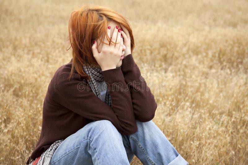 Einsames trauriges red-haired Mädchen am Feld stockfoto