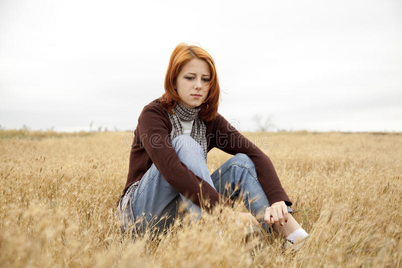 Einsames trauriges red-haired Mädchen am Feld lizenzfreie stockbilder
