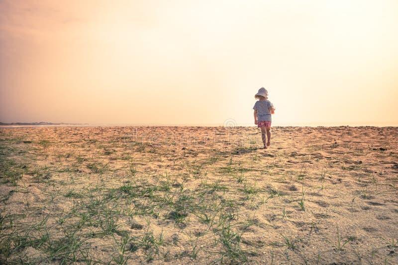 Einsames verlorenes Kinderkleinkind, das allein in den Sandd?nen erforschen Kindheitsreiselebensstil steht stockfotos