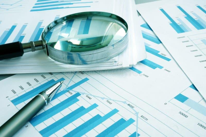 Einschätzung und Rechnungsprüfung Geschäftspapiere mit Finanzdiagrammen und Lupe lizenzfreies stockfoto