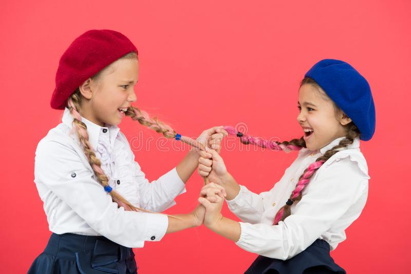 Einschüchterung und Angriff Freche Kinder, die Zöpfe auf rosa Hintergrund ziehen Kleine Mädchen mit Einschüchterungsverhalten stockfoto