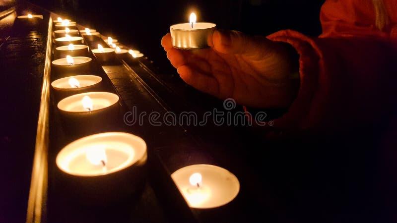 Einsetzen der Kerze auf eine Basis in eine Kirche stockfotografie