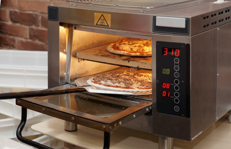 Einsetzen der Pizza in Ofen stockfoto