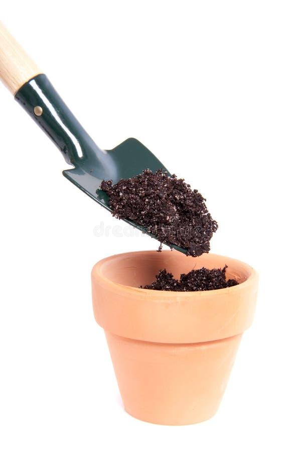 Einsetzen des Bodens in einen Terrakottapotentiometer stockfoto