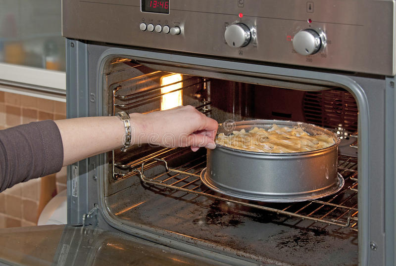 Einsetzen einer Torte in den Ofen stockbild