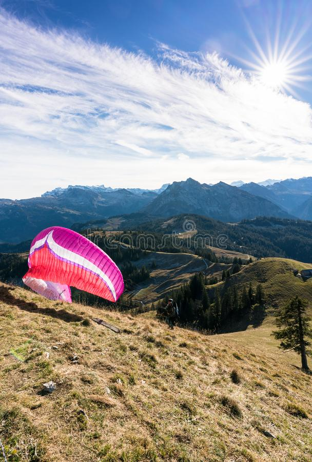 Einsiedeln, SZ / Switzerland - November 25, 2018: man with paraglider preparing for take off from a high mountain peak during an i royalty free stock photos