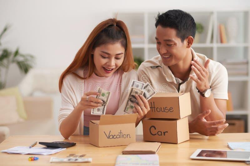 Einsparungs-Geld des glücklichen Paars lizenzfreie stockbilder