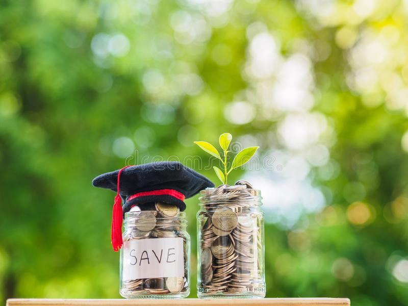 Einsparungs-Geld für Bildungs-Konzept Münzen im Glasgefäß mit Absolventen lizenzfreie stockbilder