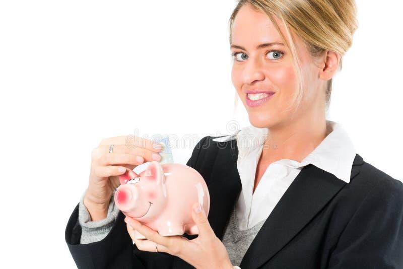 Einsparungsgeld, Frau mit einem Sparschwein stockbild