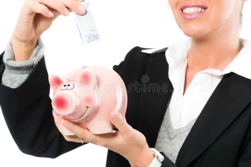 Einsparungsgeld, Frau mit einem Sparschwein stockfotografie