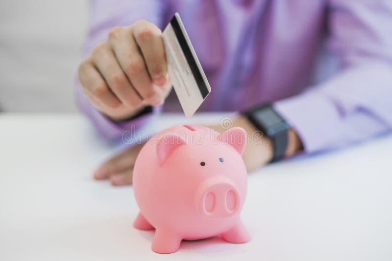 Einsparungsgeld, Geschäftsmann, der Sparschwein und Kreditkarte hält stockbild