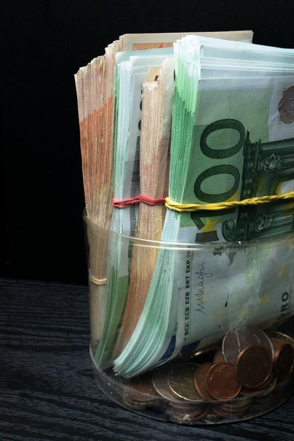 Einsparungsgeldkasten mit Eurobanknoten, Cents Banknoten der Europäischen Gemeinschaft Eurobargeldhintergrund lizenzfreies stockfoto