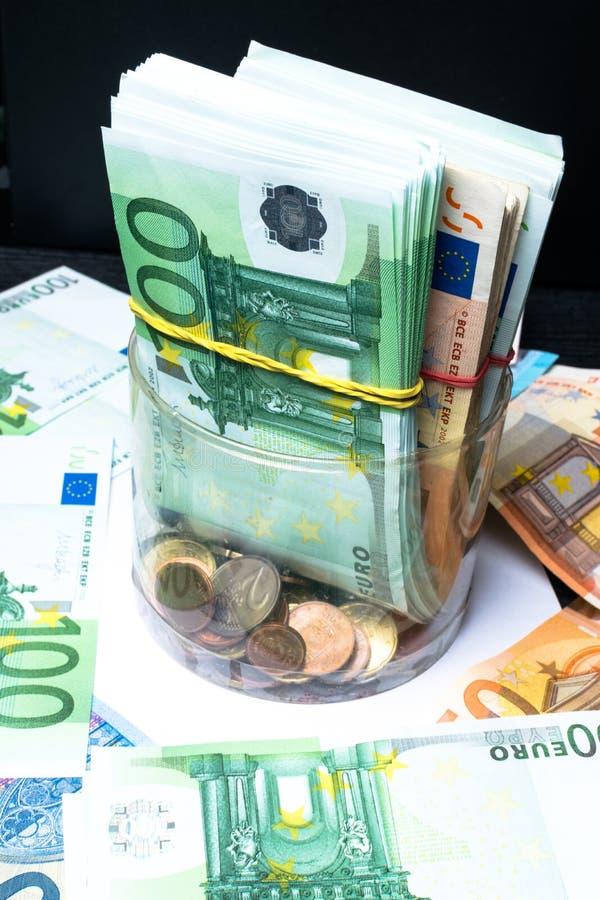 Einsparungsgeldkasten mit Eurobanknoten, Cents Banknoten der Europäischen Gemeinschaft Eurobargeldhintergrund lizenzfreie stockfotos