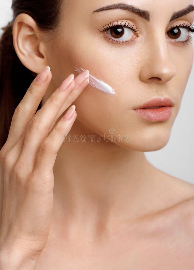 Einspritzung von botox im Gesicht der sch?nen Frau - getrenntes Wei? Frau, die Sahne auftr?gt Portr?t der jungen Frau mit kosmeti lizenzfreie stockfotos