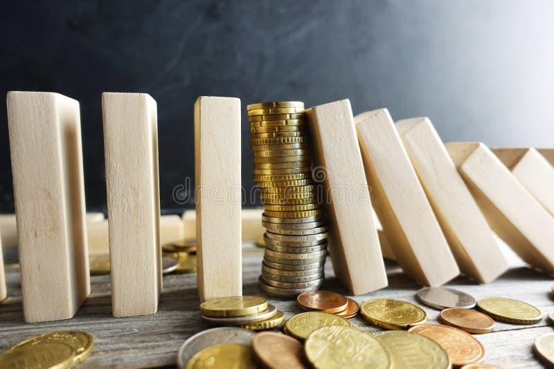 Einsturz des Wechselkurskonzeptes, mit Stapel von Münzen zwischen hölzernen Stücken als Domino stockfoto