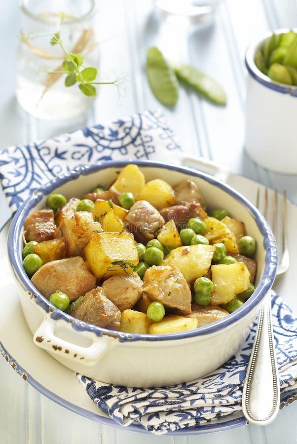 Eintopfgericht der Kartoffeln, des Schweinefleisch und der grünen Erbsen stockfotografie