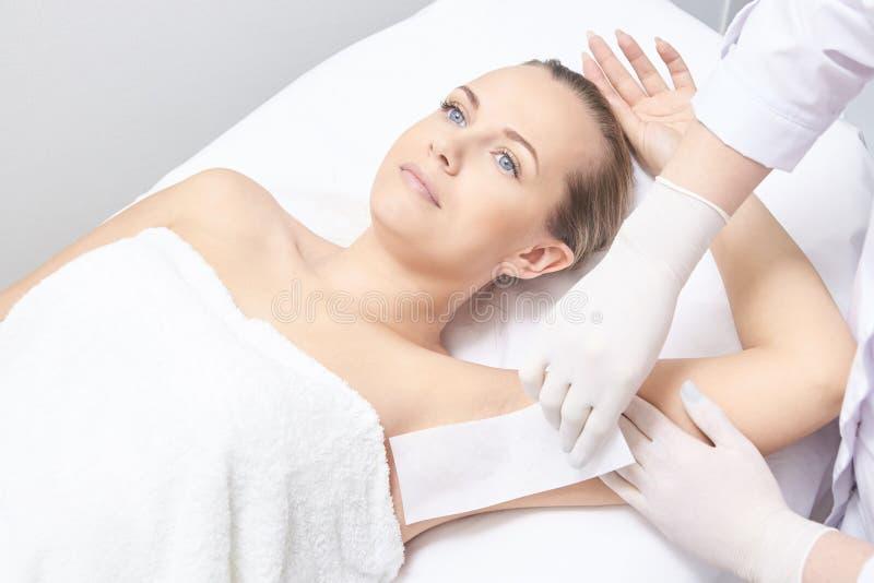 Einwachsen des Frauenbeines Zuckerhaarabbau Laser-Service epilation Verfahren des Salonwachs-Kosmetikers lizenzfreie stockfotos