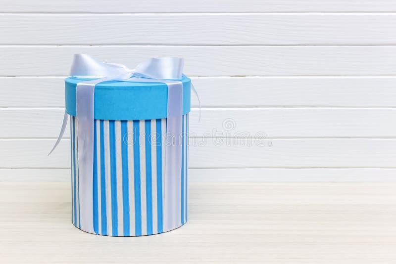 Einzelne blaue Geschenkbox auf weißer hölzerner Tabelle lizenzfreies stockfoto