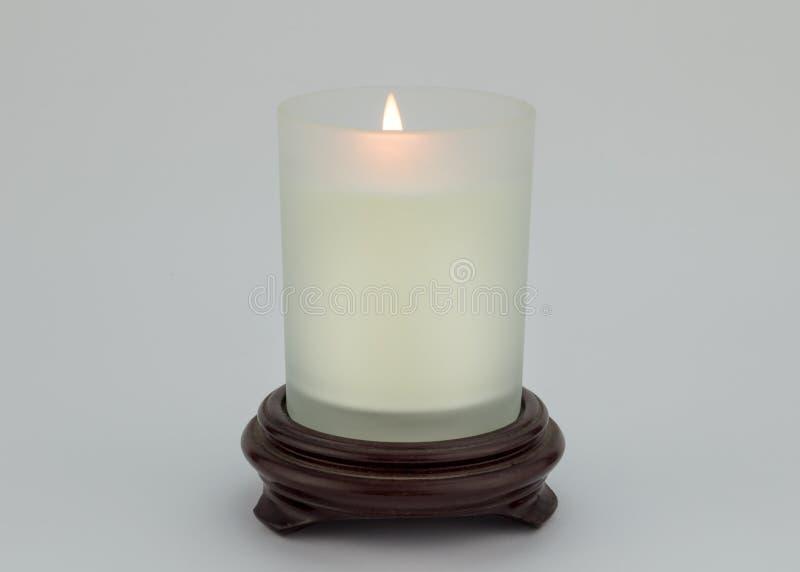 Einzelne brennende Kerze im Glas auf dem hölzernen Stand lokalisiert auf weißem backg lizenzfreie stockfotos