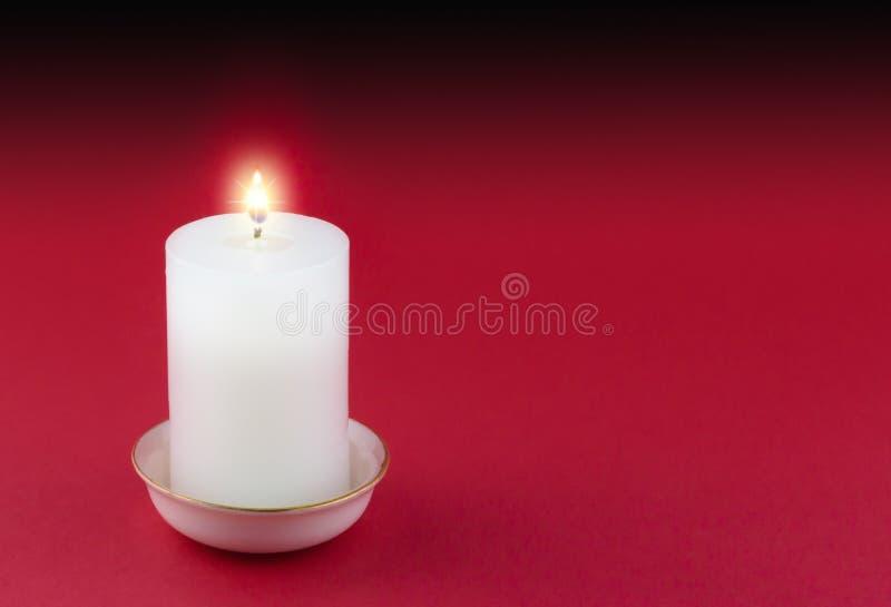 Einzelne brennende Kerze im Gold fasste weißen Halter auf Rot ein lizenzfreies stockfoto
