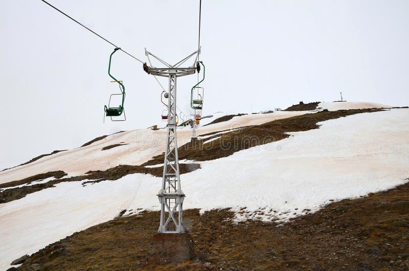 Einzelne Drahtseilbahn mit bunten Sitzen auf einem schneebedeckten Berg unterseite stockfotografie