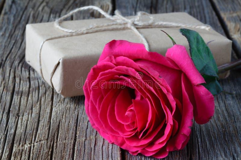 Einzelne frische Rosarose symbolisch von der Liebe und Romantik auf einem rustikalen Holztisch für einen Schatz am Valentinsgruß- stockbild