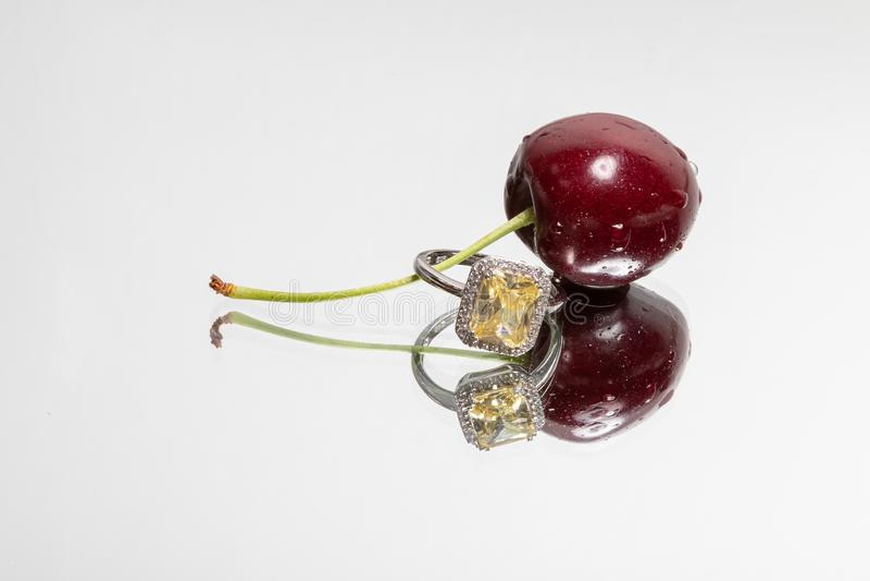 Einzelne Kirsche und Ring mit Reflexion auf einem hellen Hintergrund stockbild