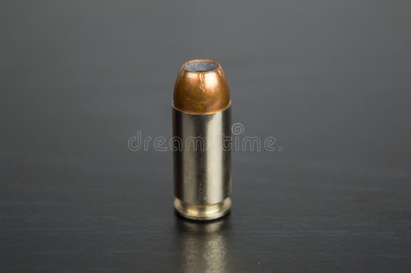 Einzelne Kugel für ein Gewehr auf einer schwarzen Tabelle stockbild