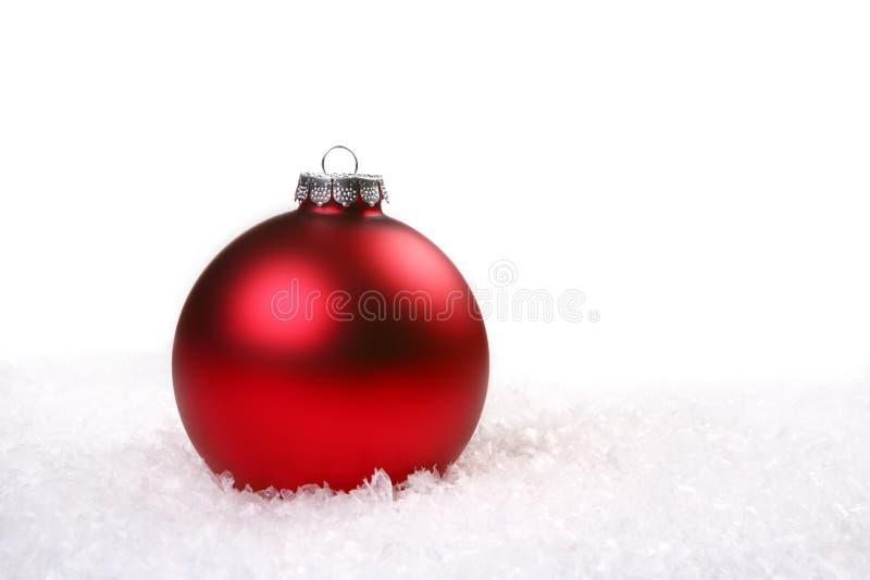 Einzelne rote glänzende Weihnachtsverzierung im Schnee stockfotografie