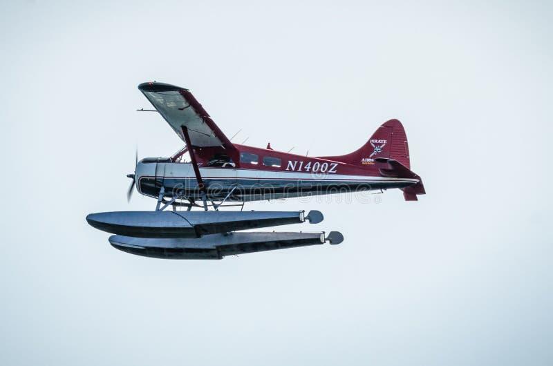 Einzelne Stützen-Flugzeug-Ponton-Flugzeugfliegen in Alaska-Bergen stockfotos