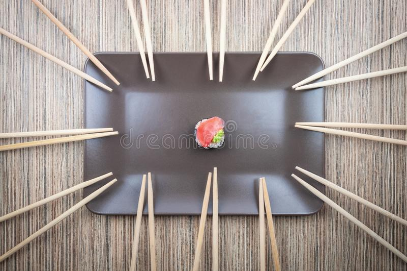 Einzelne Sushirolle in der Platte mit vielen von Essstäbchen auf Holztisch stockbilder