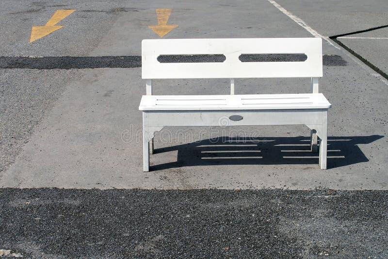 Einzelne weiße Holzbank wird in Nachmittagssonnenlicht auf konkreten Boden des leeren Parkplatzes, dort sind gelbes Pfeilsymbol a lizenzfreie stockbilder