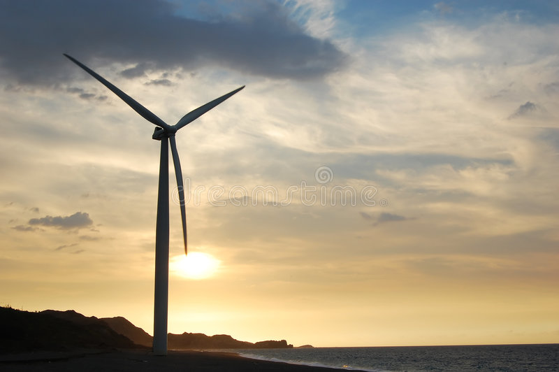Einzelne Windturbine am Sonnenuntergang stockfotografie